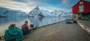 Man on his laptop, sitting on a pier overlooking a mountain, who has found the perfect place for remote work during the holidays.