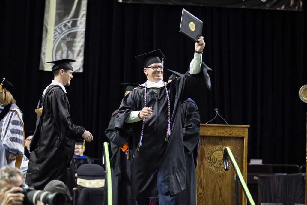 A master's student holds his degree during the 2018 UCCS spring commencement ceremonies