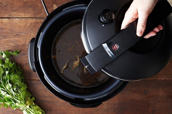 Holding a lid above a pressure cooker.