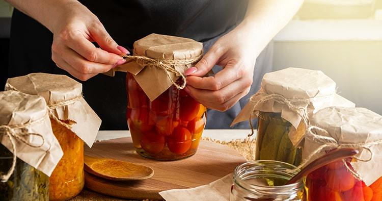 Young woman cans and pickles vegetables