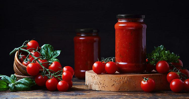 Homemade tomato sauce in a glass jar, tomatoes and herbs on its side
