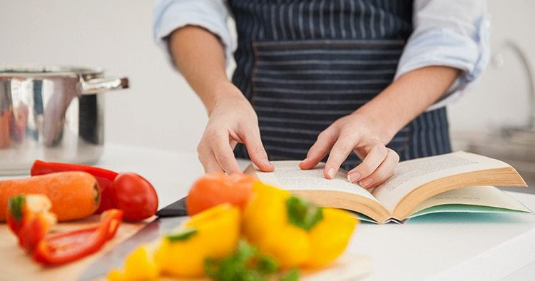 Woman looking in a old recipe book