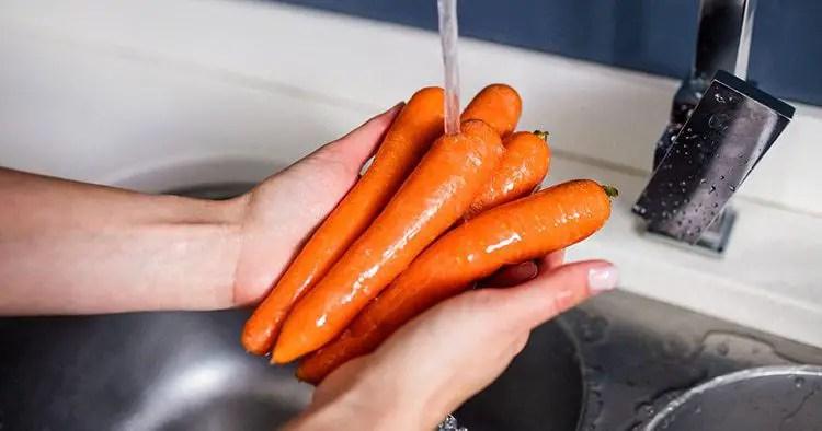 Cropped image of woman washing carrots at kitchen washbasin
