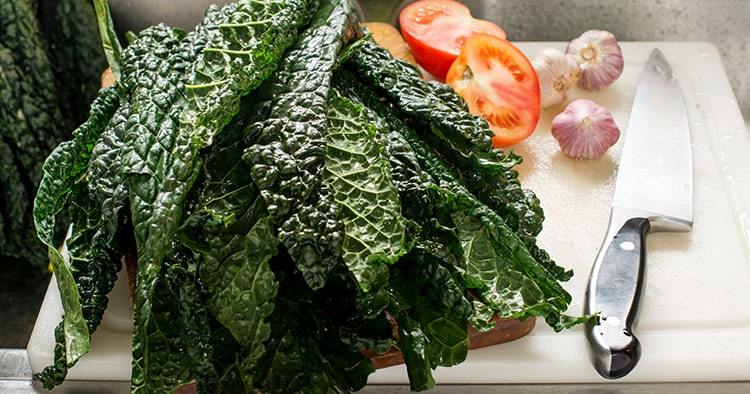 Fresh Organic Kale Leaves on Wooden Cutting Board with Knife