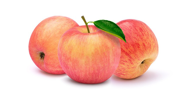 Closeup three whole pink fuji apples with green leaf isolated on white background