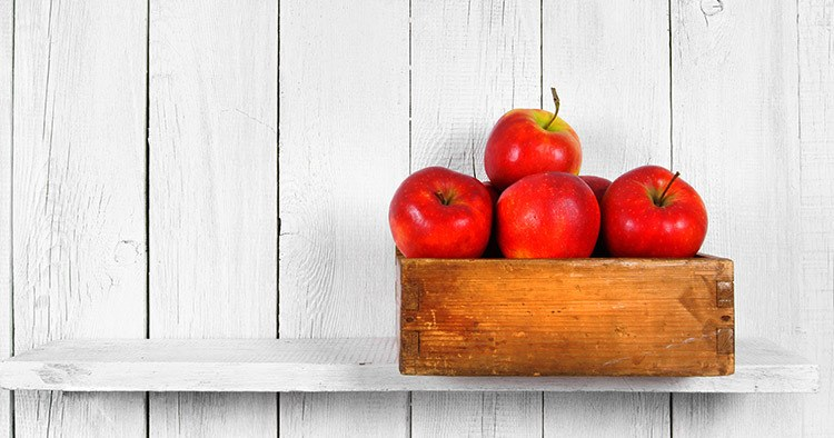 Apples in a box on a wooden shelf.