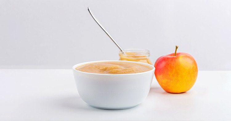 Fresh homemade applesauce in white bowl and jar with fruit puree on white table