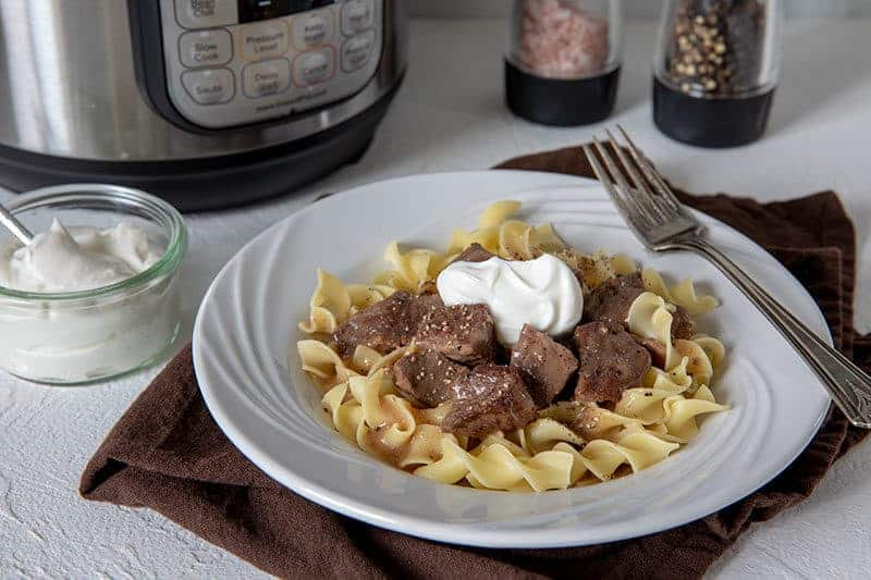 Sirloin-Tips-in-Gravy over noodles served on a white plate with a fork