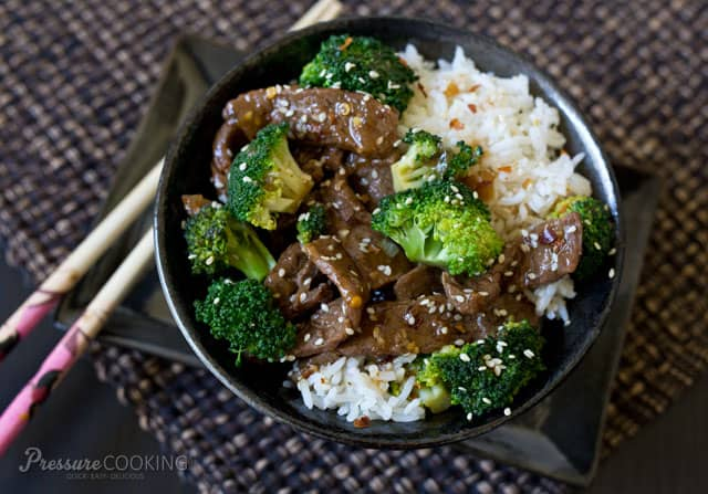 A bowl of food with rice and broccoli, with Beef and Sauce