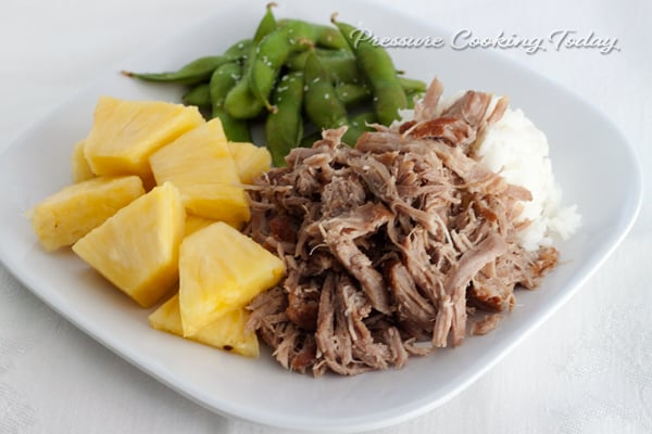 Pressure Cooker (Instant Pot) Kalua Pork on a white plate with pineapple chunks and snap peas