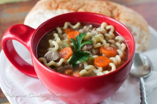 turkey noodle soup in a red bowl