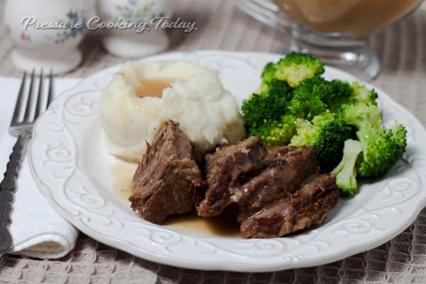 Pressure Cooker Pot Roast served on a white plate with mashed potatoes and broccoli