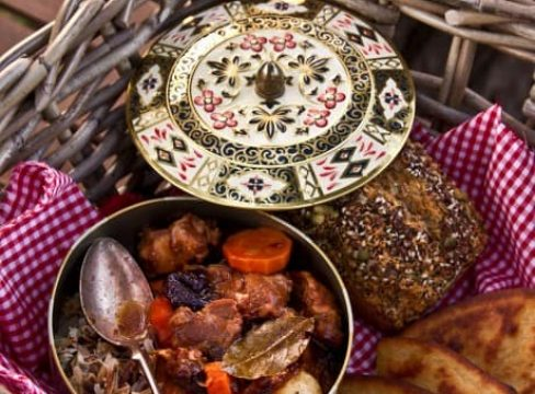 Pressure Cooker ((Instant Pot) Lamb Stew with Dried Plums in a decorative pot with a spoon