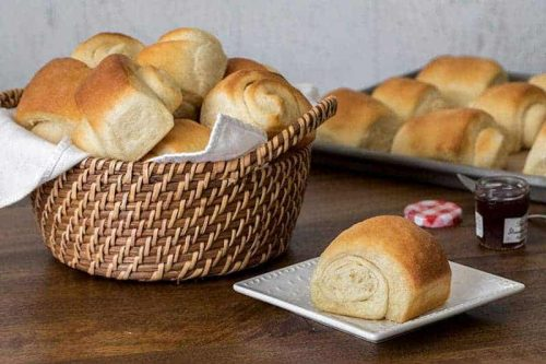 A basket of Lion House Rolls with on roll on a plate