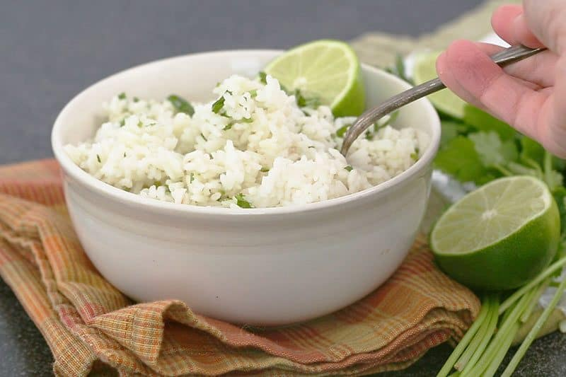 a white bowl full of Instant Pot cilantro lime rice, with green limes on the side