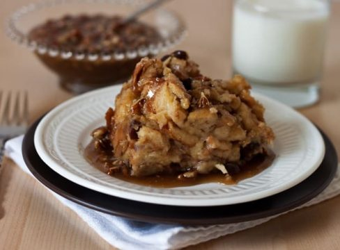 Pressure Cooker (Instant Pot) Cinnamon Raisin Bread Pudding with Caramel Pecan Sauce on a white plate