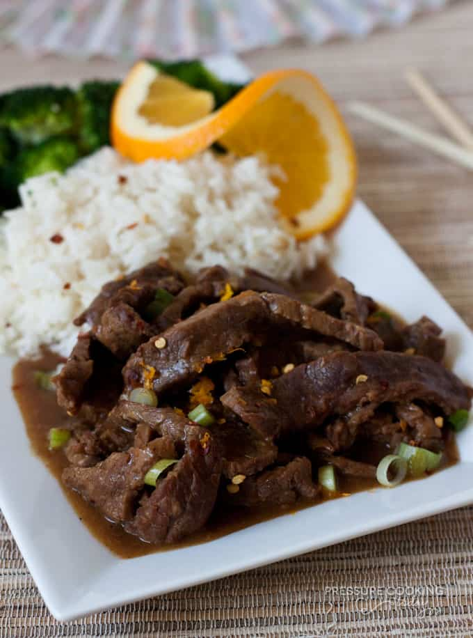 Pressure Cooker (Instant Pot) Spicy Orange Beef with a side of rice and an orange slice on a white serving dish