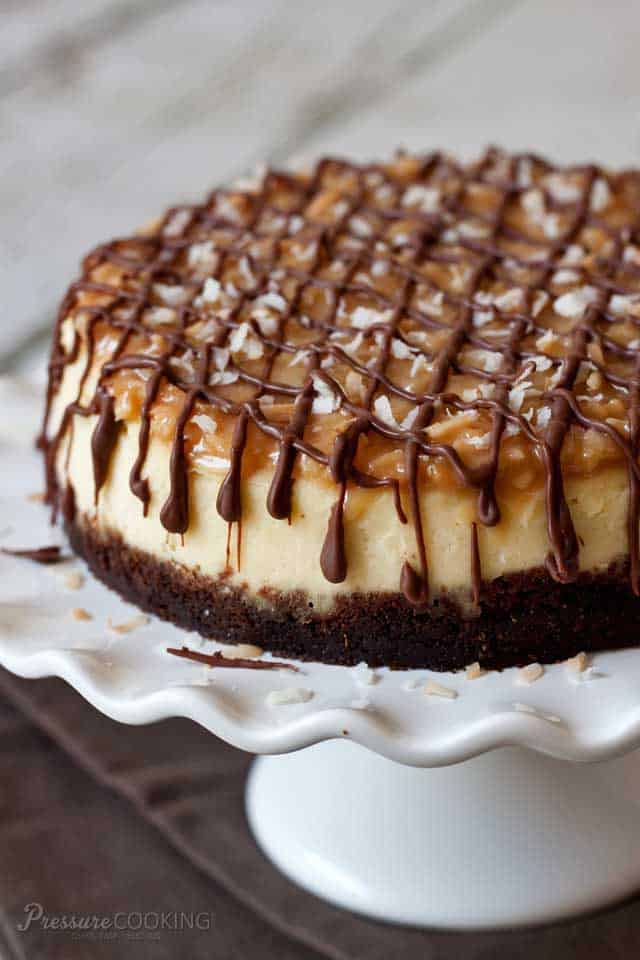 Pressure Cooker Samoa Cheesecake on a white cake stand