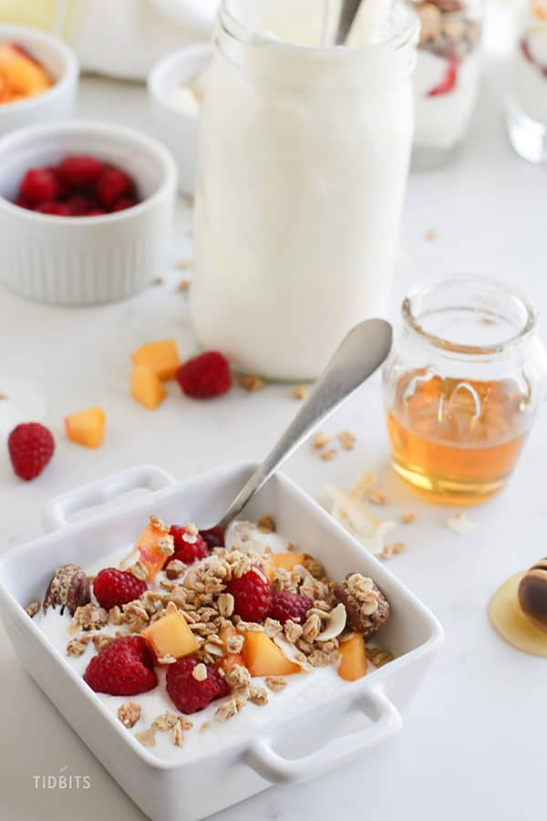 A close up of a plate of food on a table, with Yogurt and Granola