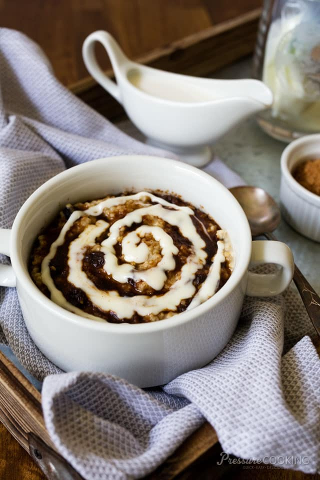 white dish of steel cut oats with cinnamon and a swirl of cream cheese frosting on top