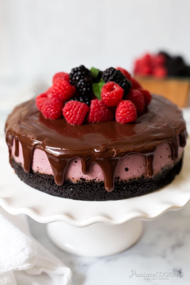 raspberry cheesecake covered in dark chocolate ganache and fresh raspberries and blackberries, sitting on a cake stand