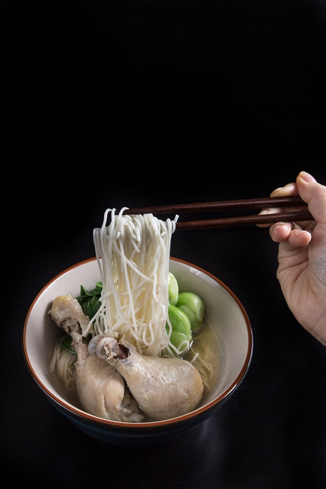 Asian Bok Choy Chicken Noodle Soup in a bowl. Pressure cooked noodles being held with chopsticks