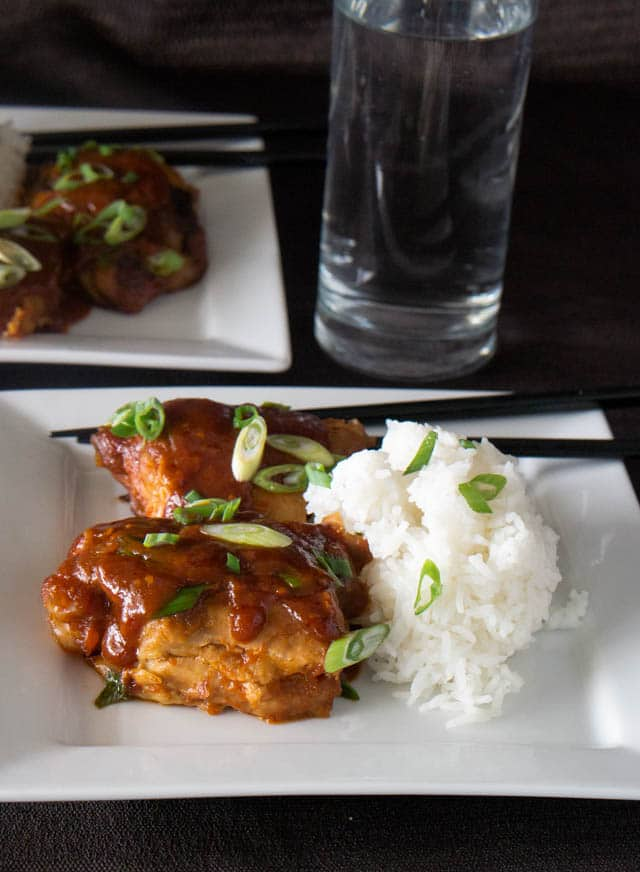 two white dinners plates with Korean-style chicken thighs and white rice, all made in an electric pressure cooker