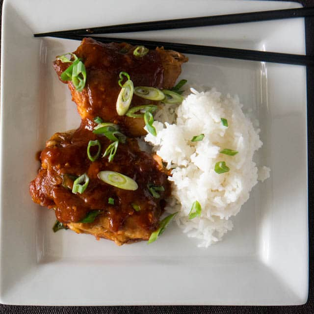 white dinner plate with 2 Asian spiced chicken thighs and fluffy white rice, all made in an Instant Pot electric pressure cooker