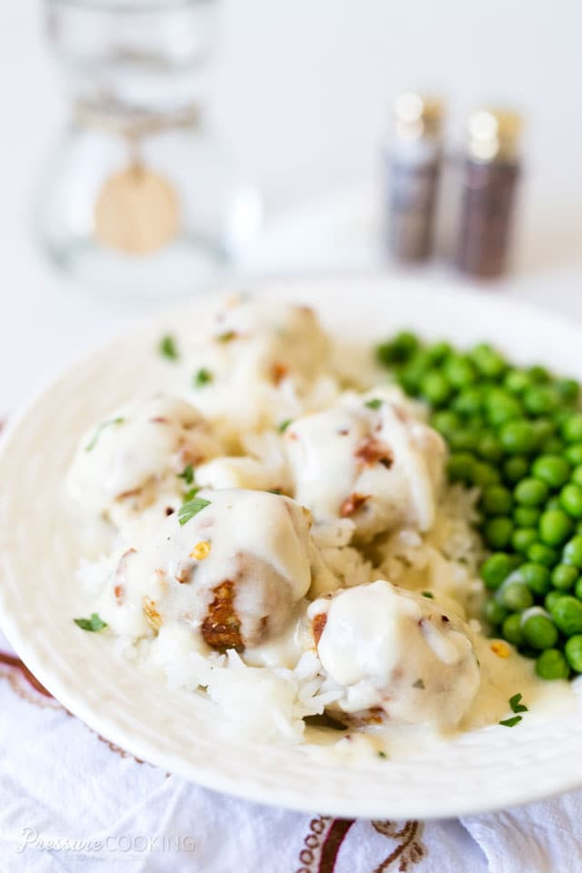 plate of chicken Parmesan meatballs in creamy ranch sauce along with a side of peas