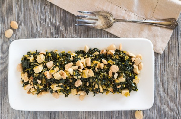 white platter of Pressure Cooker Kale served with baked tofu and almonds