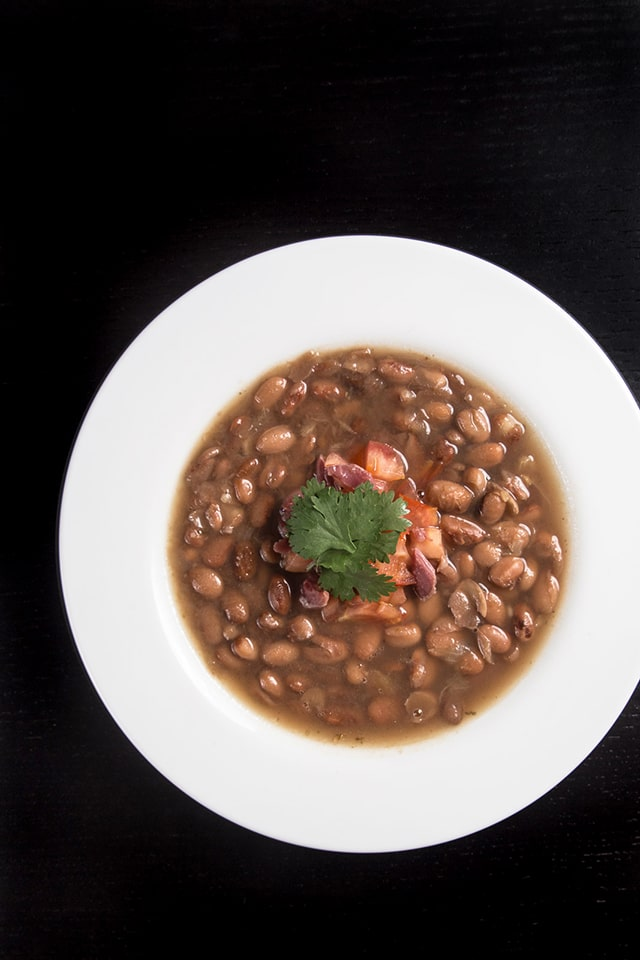 Overhead image of a white bowl of Smoky Ham Hock and Pinto Bean Soup made in an Instant Pot