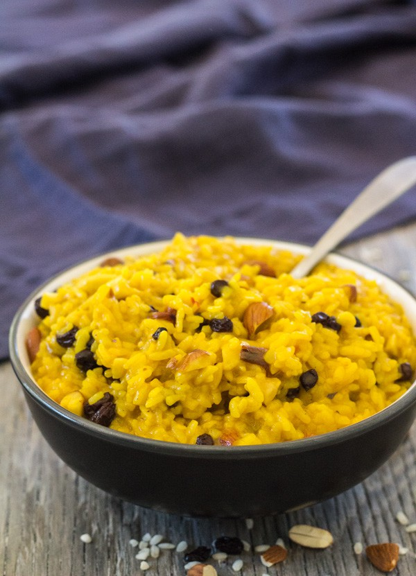 black serving bowl filled with bright yellow Saffron Risotto with Almonds and Currants