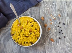 Instant Pot Saffron Risotto with Almonds and Currants in a white bowl with spoon