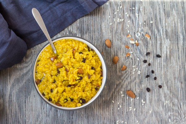 serving bowl filled with Pressure Cooker Saffron Risotto with Almonds and Currants