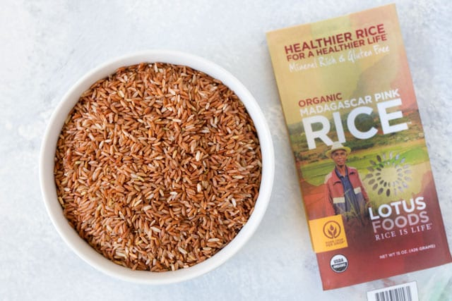 white bowl with uncooked grains of Madagascar pink rice
