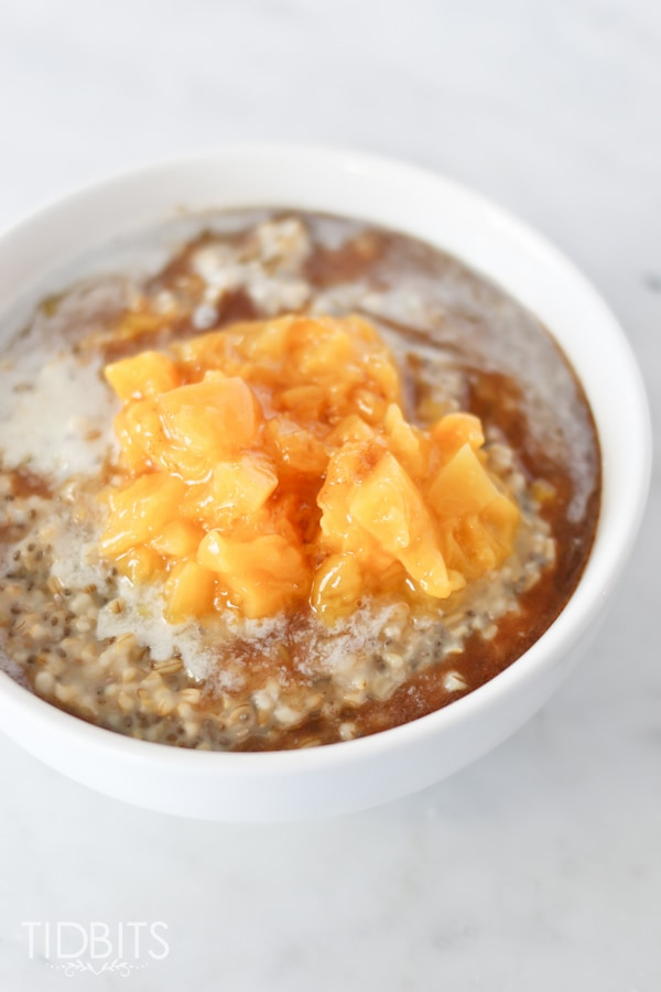 Steel Cut Oats served in a white bowl with peaches and cream