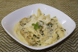 spinach-artichoke-pasta-with-chicken in a white bowl