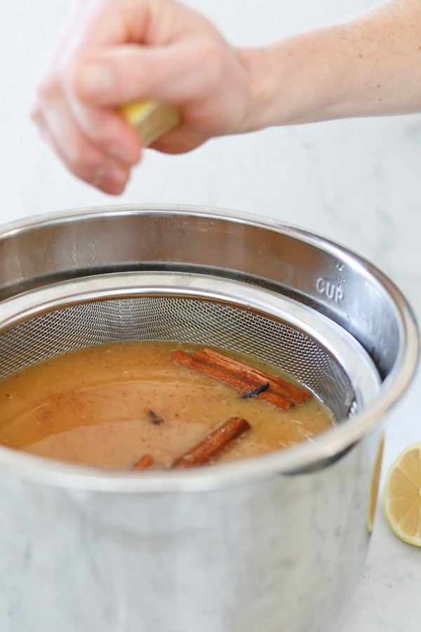 wassail that was made in an Instant Pot is strained to remove citrus pulp