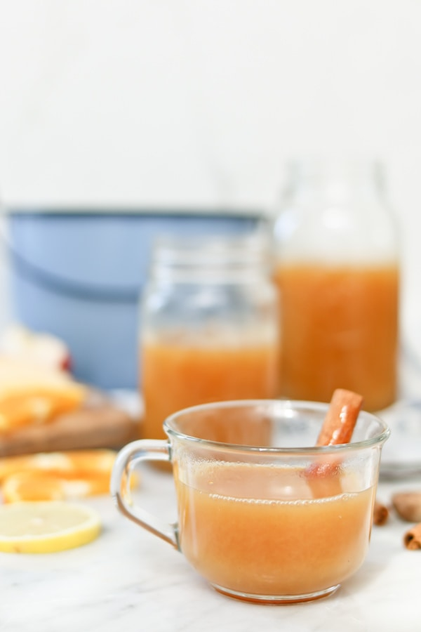 mug of electric pressure cooker wassail, garnished with a cinnamon stick