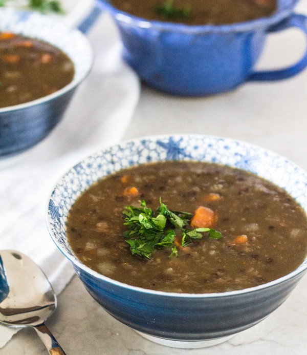 blue soup bowl with Hearty Lentil Beer Soup, made in an Instant Pot