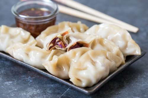 A tray of food on a plate, with Steamed dumplings