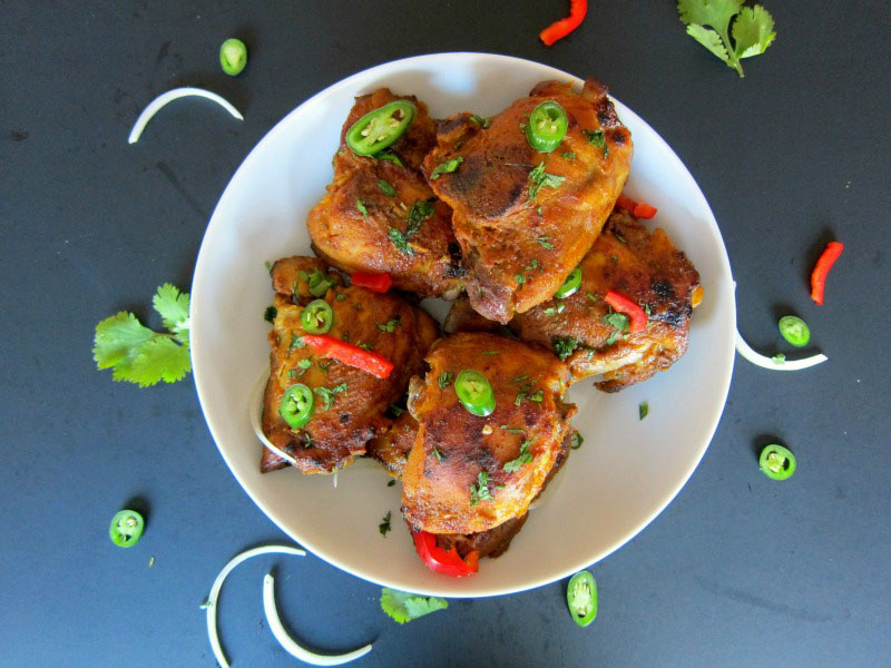 5 pieces of Pressure Cooker Tandoori Chicken on a plate, garnished with jalapenos