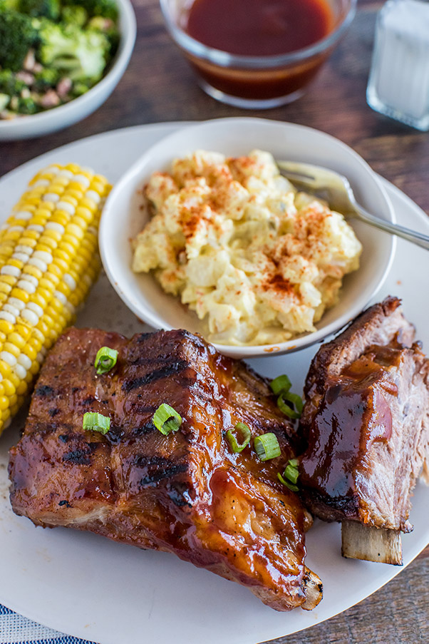 A plate of Baby Back Ribs, corn on the cob, and potato salad ready to serve.