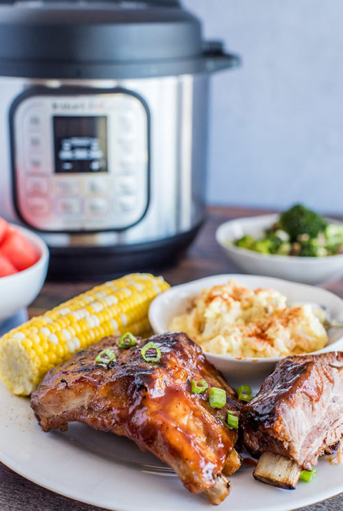 A plate of food on a table with Pork ribs, corn on the cob, and potato salad with Instant Pot in background.