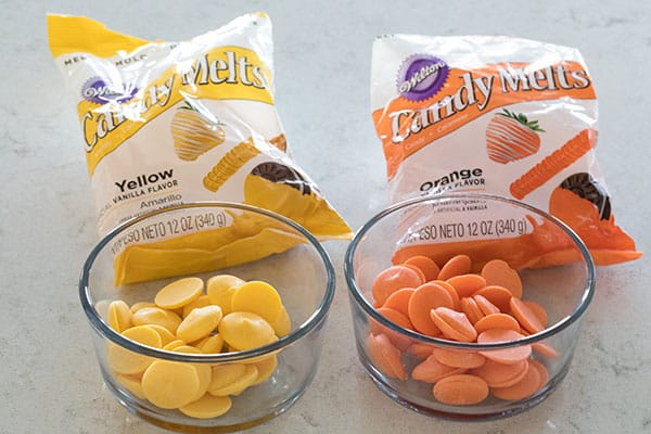 Orange and yellow candy melts in bowls with packages behind them