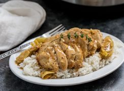 Pressure Cooker (Instant Pot) Artichoke Chicken over rice on a white plate with fork