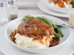 pork and gravy served on a white plate with  green beans