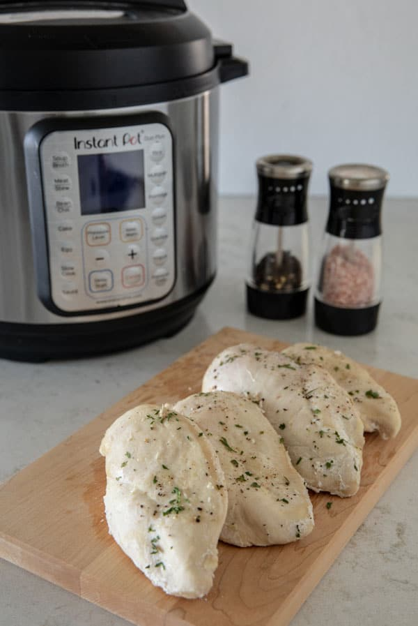 Instant Pot Pressure Cooker Frozen Chicken Breasts on a cutting board with Instant Pot and salt and pepper in the background.