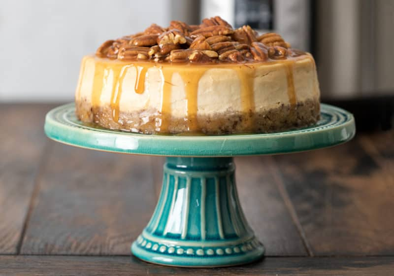Pressure Cooker Caramel Pecan Cheesecake on an aqua colored cake stand