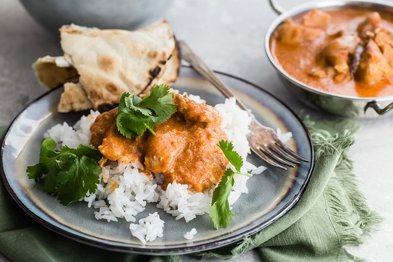 Pressure Cooker / Instant Pot Butter Chicken served on a bed of basmati rice with a side of naan